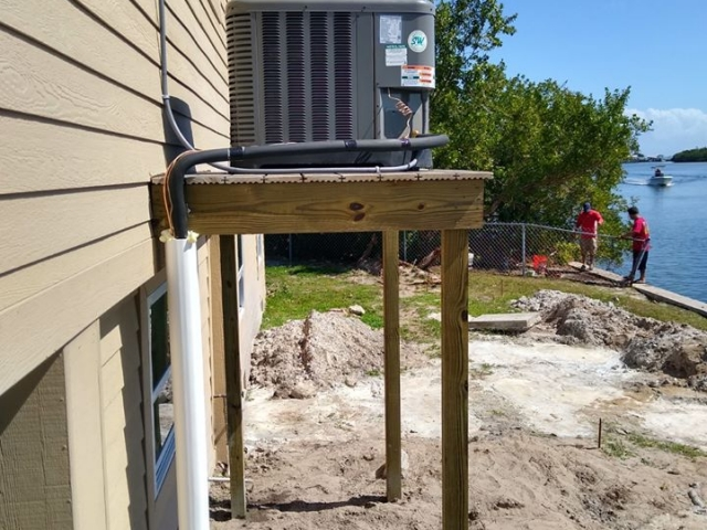 Elevated air conditioner installation on stilt home.